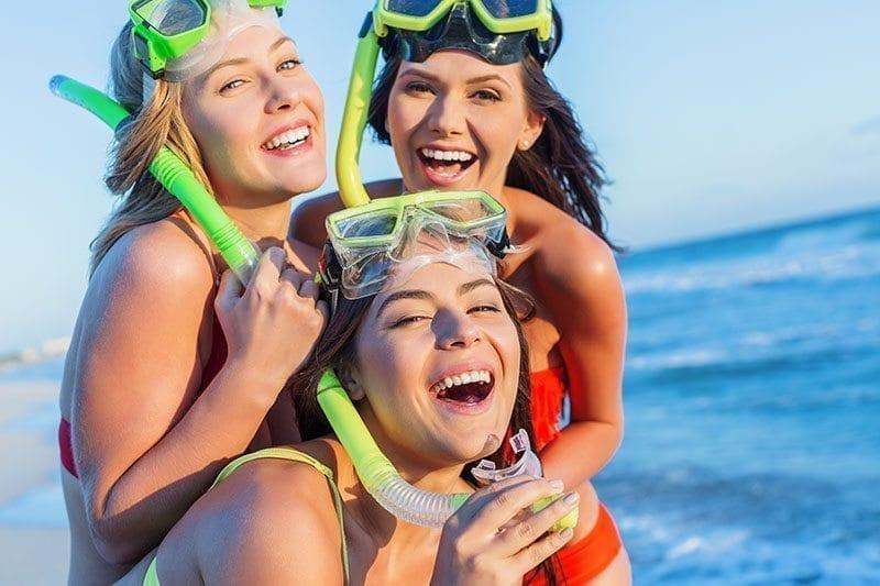 Three women on beach with snorkels smilnig.