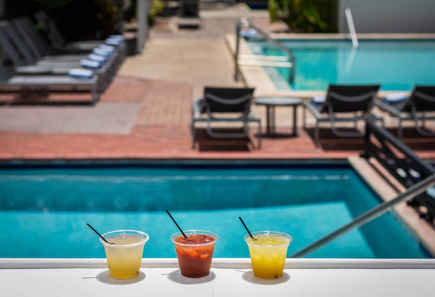 Mixed drinks sitting poolside.